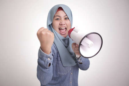 Young Asian muslim woman wearing hijab shouting with megaphone and pointing to camera. Leader supporter or protester concept. Close up body portrait