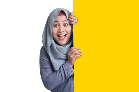 Young Asian muslim businesswoman smiling and peeking behind blank white advertising billboard wign board with copy space