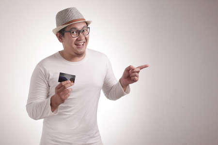 Asian man smiling at camera while holding credit card and pointing to the side with copy space, presenting something concept