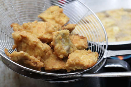 Cooking deep fried tempeh, Indonesian traditional meal, tempe goreng or gorengan. Deep frying chicken nugget