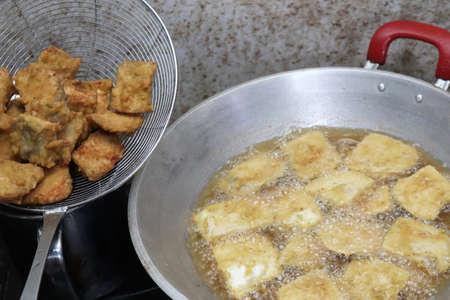 Cooking deep fried tempeh, Indonesian traditional meal, tempe goreng or gorengan. Deep frying chicken nugget
