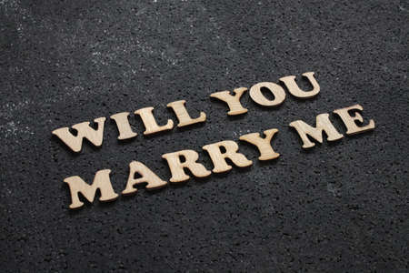 Will you marry me. Romantic couple message words lettering. Mariage proposal words arranged with wooden alphabet on black background