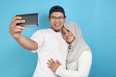 Portait of happy Asian muslim couple making selfie and smiling, husband and wife hugging full of love, family concept