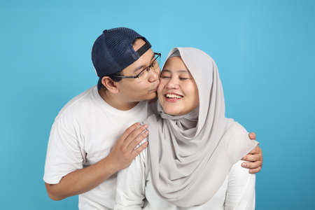 Portait of happy Asian muslim couple smiling, husband and wife hugging and kissing full of love, family concept Stock Photo