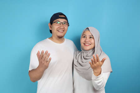 Portait of happy Asian muslim couple smiling, looking up and dreaming, husband and wife hugging full of love, family concept