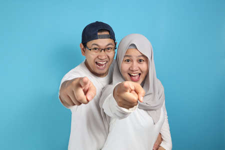 Portait of happy Asian muslim couple smiling and pointing to camera, husband and wife hugging full of love, family concept