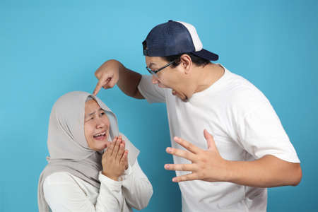 Portrait of funny Asian muslim couple having conflict, wife and husband fight, violence in family, wife afraid to her husband concept