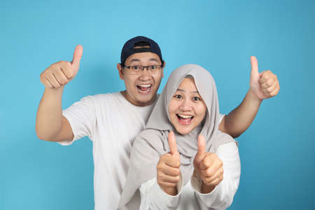 Portait of happy Asian muslim couple smiling and shows thumbs up gesture, husband and wife hugging full of love, family concept Stock Photo