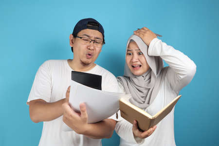 Portrait of Asian young muslim couple checking analyzing their family financial management report, young family housband and wife confused to have bad financial