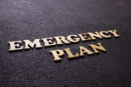 Emergency Plan. Motivational internet business words quotes; wooden lettering typography concept on black background