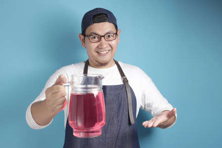 Portrait of Asian male chef or waiter smiling while offering fresh red syrup beverage, offering cocktail concept, against blue background