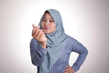 Portrait of happy smiling Asian muslim woman doing cash, rich or money gesture Фото со стока