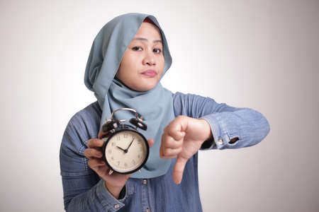 Young Asian muslim woman wearing  hijab shows clock, angry disappointed expression with thumb down gesture. Isolated on white