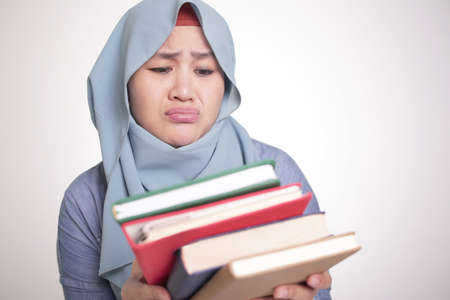 Portrait of cute Asian muslim woman sick and tired reading too much books Stok Fotoğraf