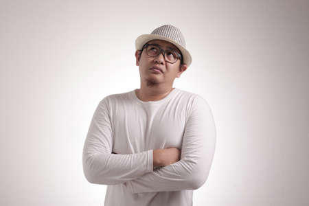 Young Asian man casual white shirt shows disappointed gesture, half body portrait over white background