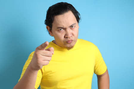 Portrait of Asian man showing cynical unhappy angry facial expression pointing forward, giving warn