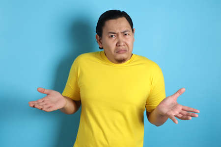 Photo image of funny Asian man with shrug shoulder up gesture, showing i don't know or rejection