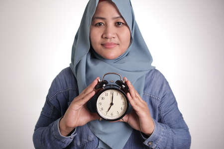 Young Asian muslim woman wearing hijab holding a clock, smiling expression, on time management concept