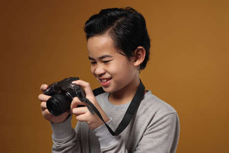 Happy Asian boy doing photography leisure activity, kid as photographer taking picture with his digital camera, against yellow background