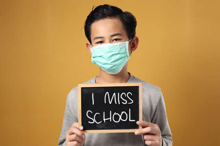 Student boy miss school during covid coronavirus pandemic lockdown qurantine, bored to stay at home too long, boy wearing mask Foto de archivo
