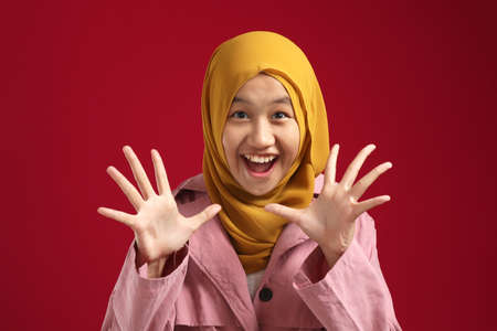 Portrait of young Asian teenage muslim girl wearing red hijab looked shocked surpried with big eyes and open mouth, against red background