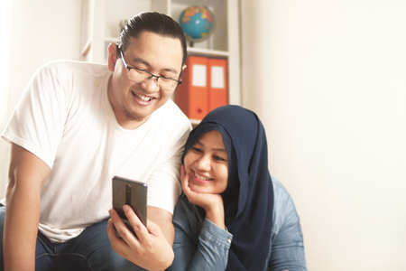 Asian muslim couple smiling happy when looking at smart phone, good news on internet concept