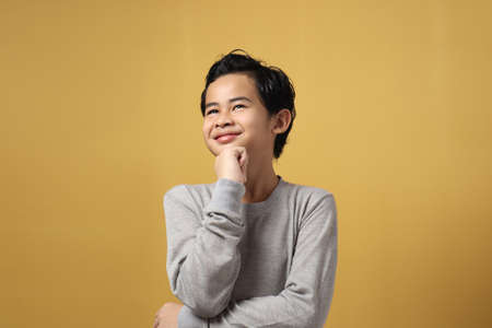 Portrait of cute Asian little boy looking up, thinking something and smile, finding good idea, against yellow background