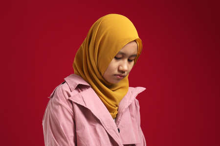 Portrait of sad young Asian teenage muslim girl wearing hijab looking down and depressed, standing against red background