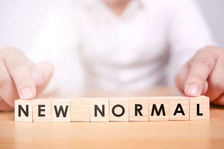 NEW NORMAL man arrange word on wooden alphabet cube with selective focus. Big change after covid-19 pandemic with social distancing