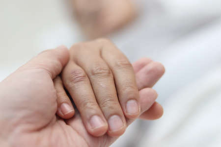 I'm here for you , doctor hand holding his patients to give love and support, selective focus with blurry background