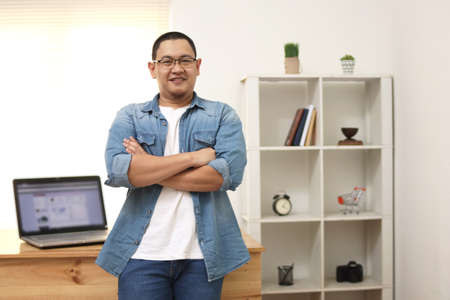 Happy succesful young Asian entrepreneur smiling at camera confidently in his home office studio, work at home concept