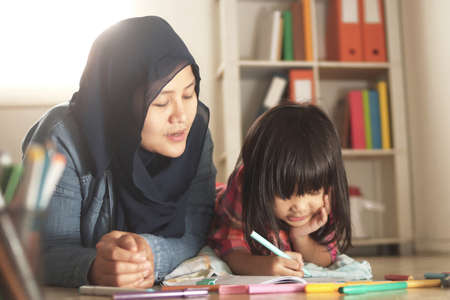 Asian muslim mother drawing with her daughter, single mom teaching baby girl, learning on the floor, happy family concept Banco de Imagens
