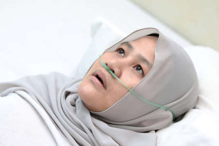 Asian muslim female patient with nasal cannula staying in hospital room alone. Uncomfortable sick woman look pensive lying in bed. Oxygen tube on her nose, hard to breath