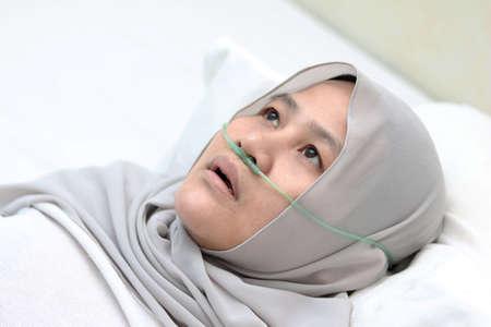 Paciente mujer musulmana asiática con cánula nasal que se queda sola en la habitación del hospital. Mujer enferma incómoda mirada pensativa acostada en la cama. Tubo de oxígeno en la nariz, dificultad para respirar
