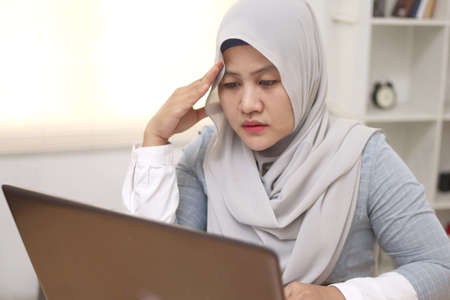 Asian muslim woman sad and frustrated to see her business report on laptop, businesswoman failure concept