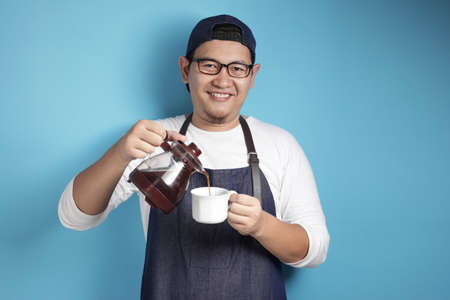 Portrait of Asian male chef or waiter smiling while pouring coffee to a cup, offering coffee concept, against blue background