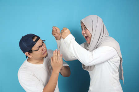 Portrait of funny Asian muslim couple having conflict, wife and husband fight, violence in family, husband afraid to his wife concept Foto de archivo