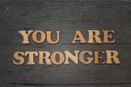 Inspirational motivational quote - You are stronger, word text typography made of wooden on grunge background