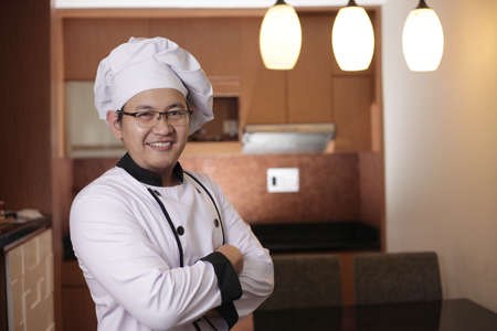 Portrait of happy proud Asian chef smiling at camera with crossed arms, chef in kitchen, successful chef in restaurant business