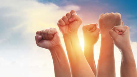 Rising fist of adult people, male and female, over dramatic blue sky with sun light, anger protest revolution inspiration motivation or teamwork concept