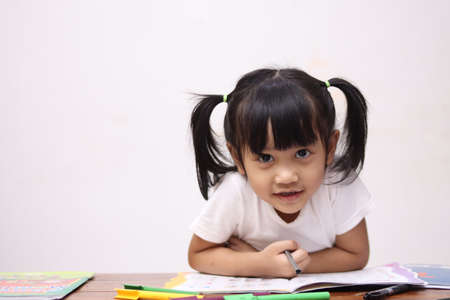 Cute adorable little Asian baby girl with pony tail hair looking at camera and smiling, happy joy excited expression when learning at home
