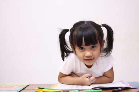 Adorable petite fille asiatique mignonne avec des cheveux de queue de cheval regardant la caméra et souriante, joyeuse expression excitée lors de l'apprentissage à la maison
