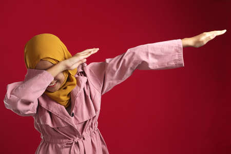 Portrait of funny young Asian muslim, teenage girl smiling and making dab movement, over red background