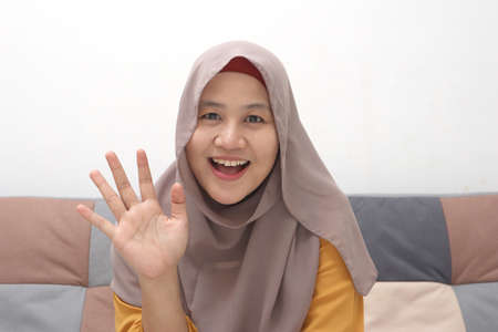 Beautiful Asian muslim lady doing selfie portrait on phone or doing video call while sitting on sofa, happy smiling cheerful expression, waving gesture Banco de Imagens