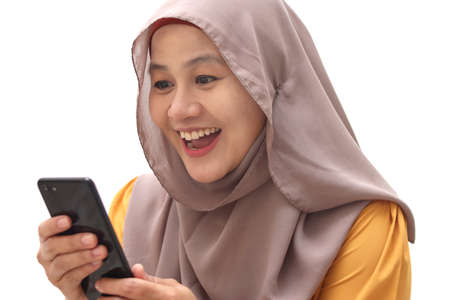 Close up portrait of young Asian muslim woman wearing hijab get good news on her phone, happy surprised expression, isolated on white 版權商用圖片
