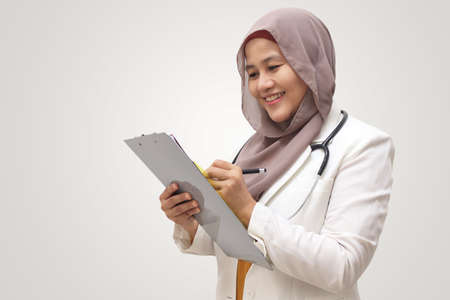 Asian muslim female doctor wearing hijab with stethoscope in white coat holding clipboard, ready to serve her medical patient, write medical record diagnosis 版權商用圖片