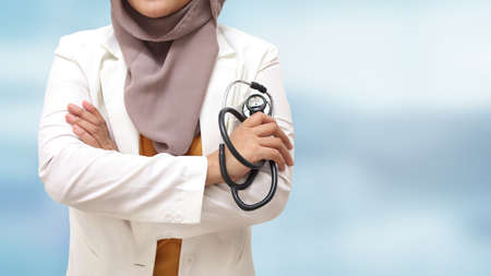 Muslim female doctor wearing hijab and suit, standing with crossed arm and holding stethoscope, succesful confident person, against blue background