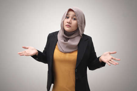 Portrait of Asian muslim businesswoman wearing hijab shows refusal or denial gesture, shoulder shrug, I don't know expression Imagens