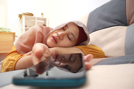 Asian muslim woman wearing hijab slept on couch with phone in her hand, too much smart phone or gadget use, mobile phone addict concept 版權商用圖片