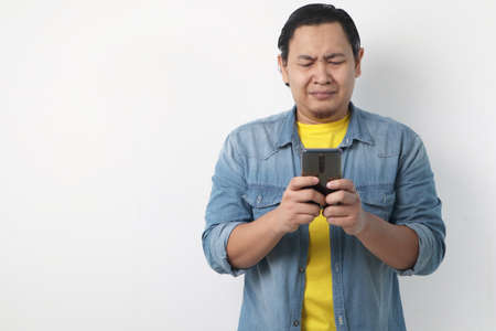 Attractive young Asian man reading texting chatting  on his phone, bad news, sad  crying expression 版權商用圖片